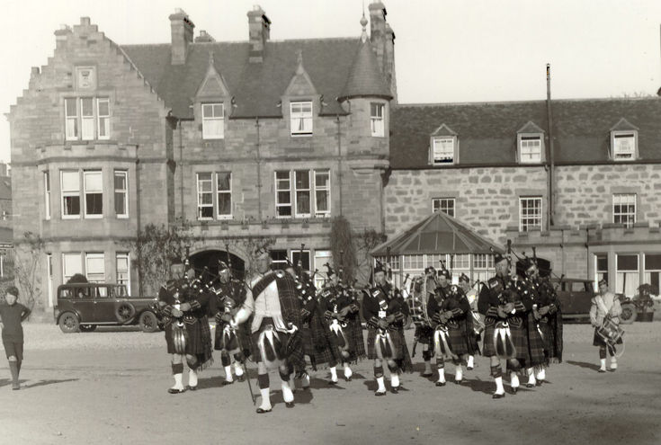 Dornoch Pipe Band parading in front of the Sutherland Arms Hotel 1930's