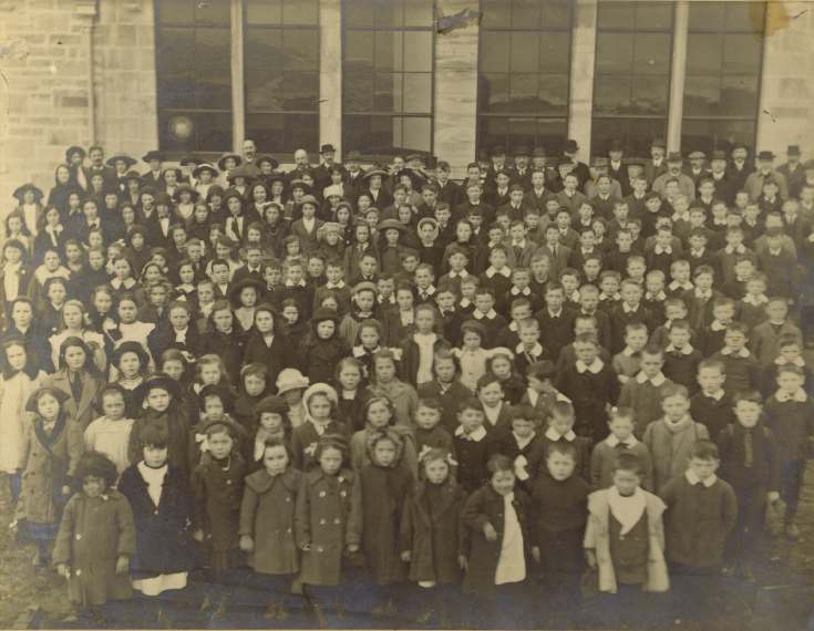 Photograph  of the pupils and staff of Dornoch Academy at opening ceremony by Lord Kennedy, 1913.