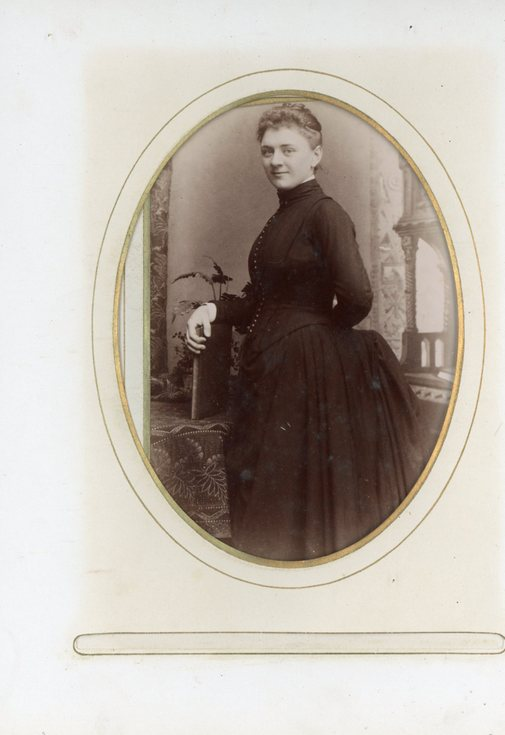 Studio portrait of a lady standing at a table