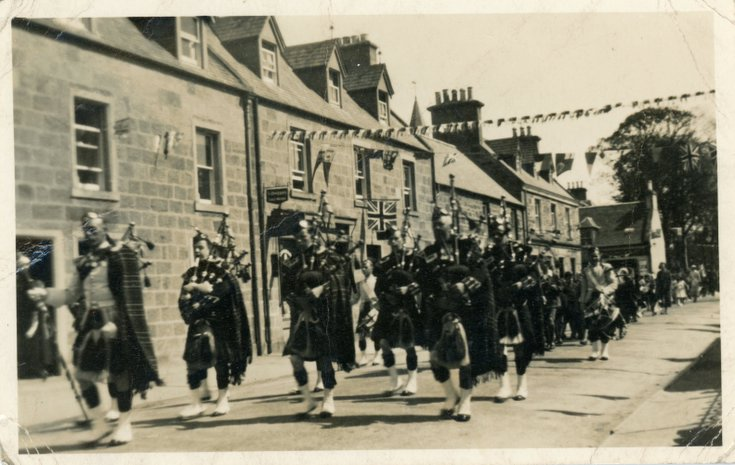 Dornoch Pipe Band marching along Castle Street
