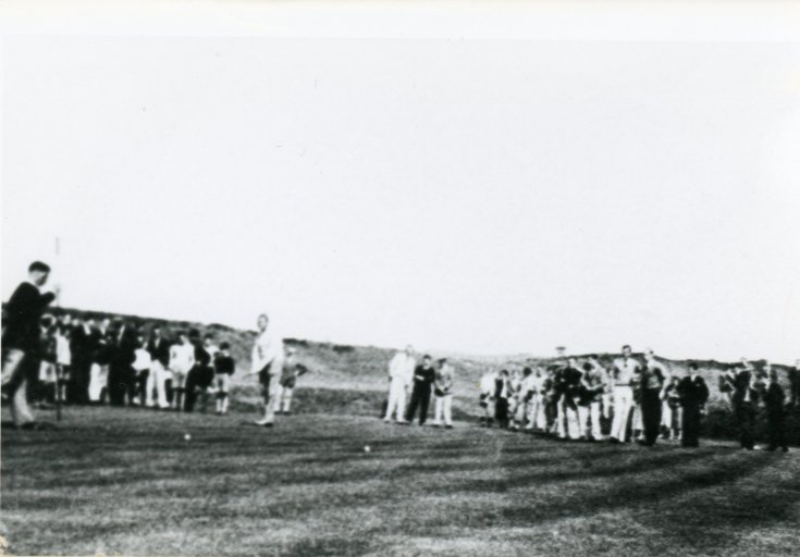 Golfers putting with a crowd of followers