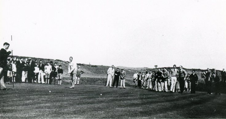 Golfer putting surrounded by spectators