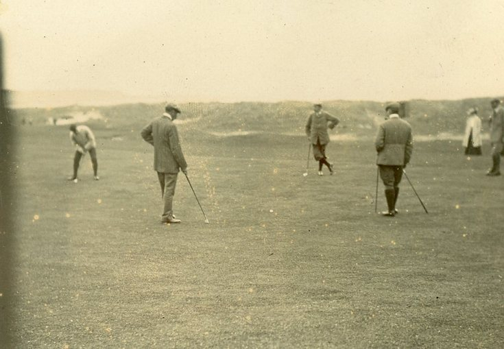 Early photograph of golfers putting