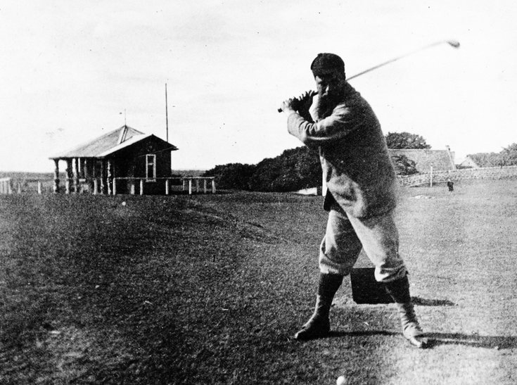 Golfer teeing off adjacent to ladies clubhouse