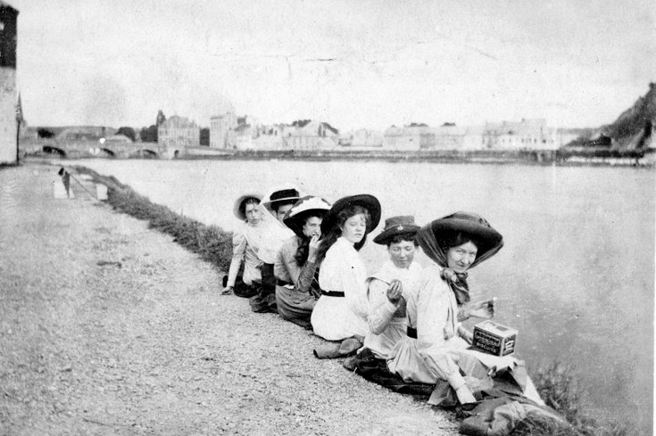 Six young ladies sitting on a river bank