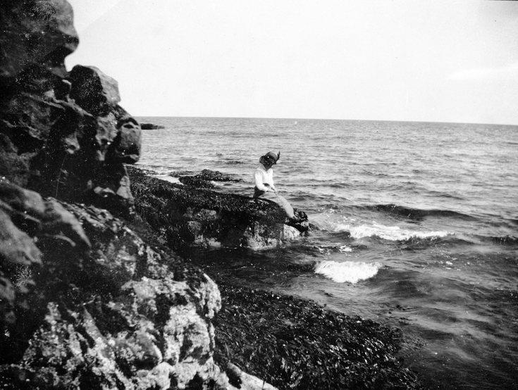 A lady sitting on the rocks at Dornoch beach