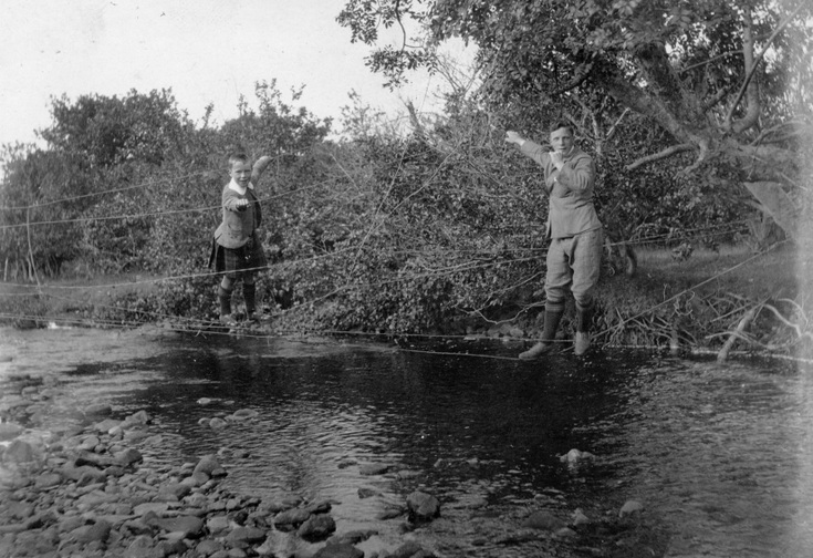 Young man + boy crossing a burn on suspended wire