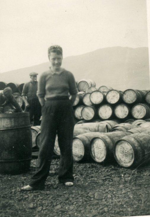 Bella Mackay standing beside a barrel stack
