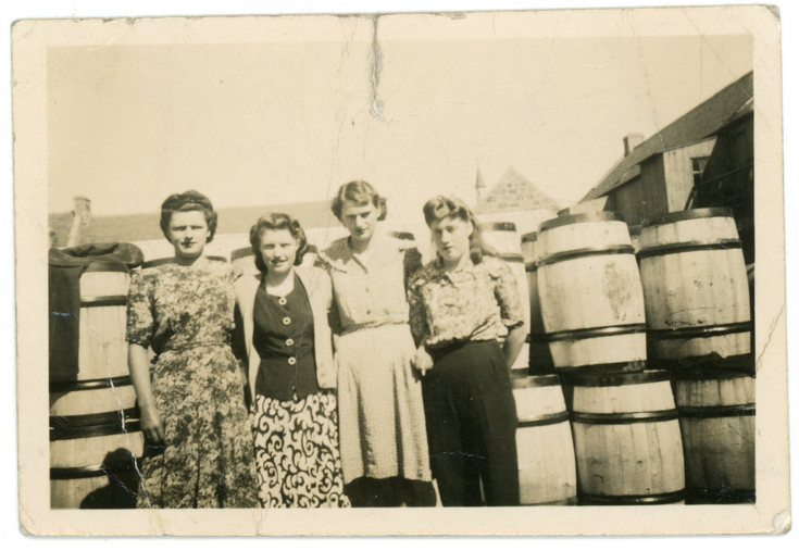 Group standing beside a barrel storage area