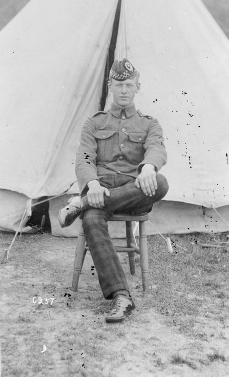Young soldier seated in front of bell tent