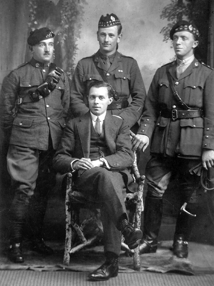 Studio portrait of three soldiers and man in suit