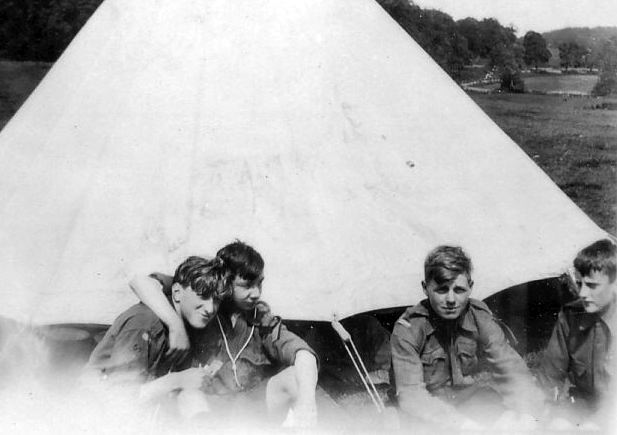 Scouts sitting outside bell tent