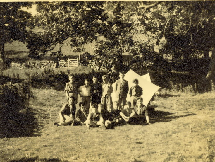 Group of scouts at a woodland camp site