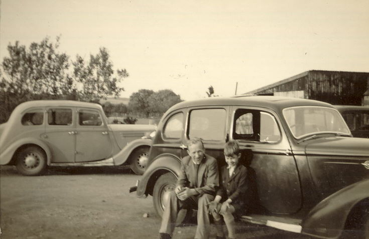 Man and Boy sitting on the running board of a car