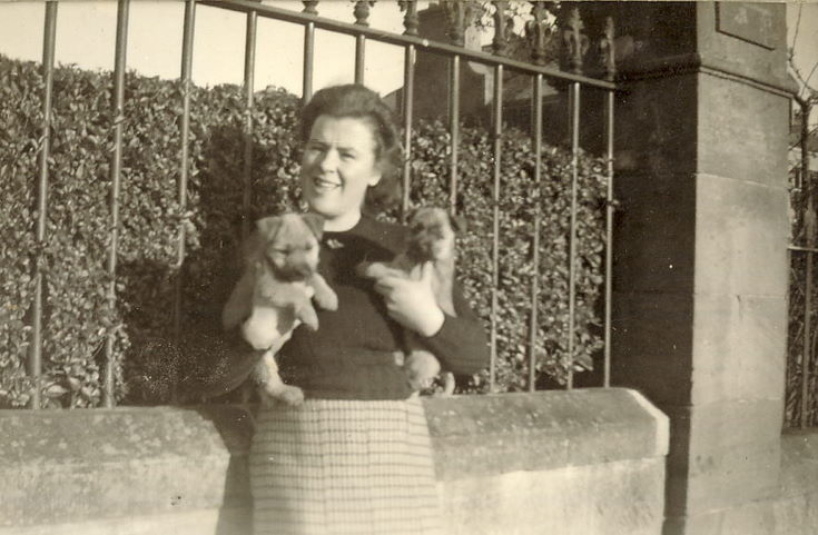 Lady holding two puppies, outside (probably)