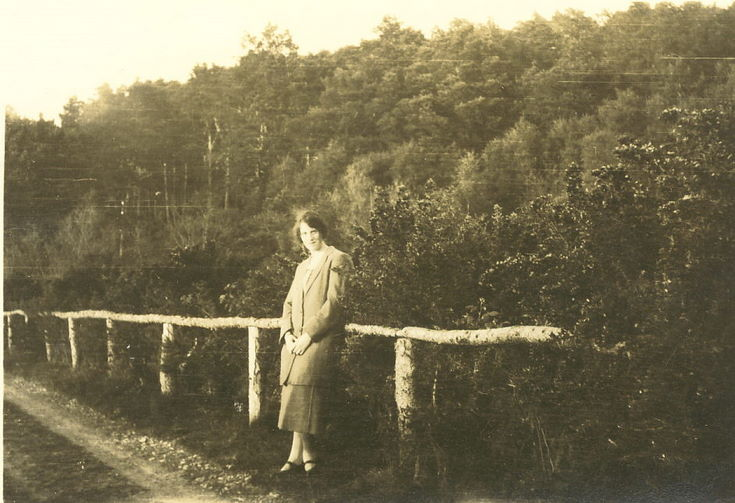 Woman standing against a single-rail fence