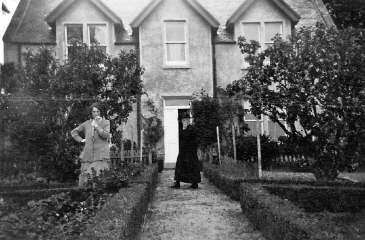 Two Ladies in the front garden of a house