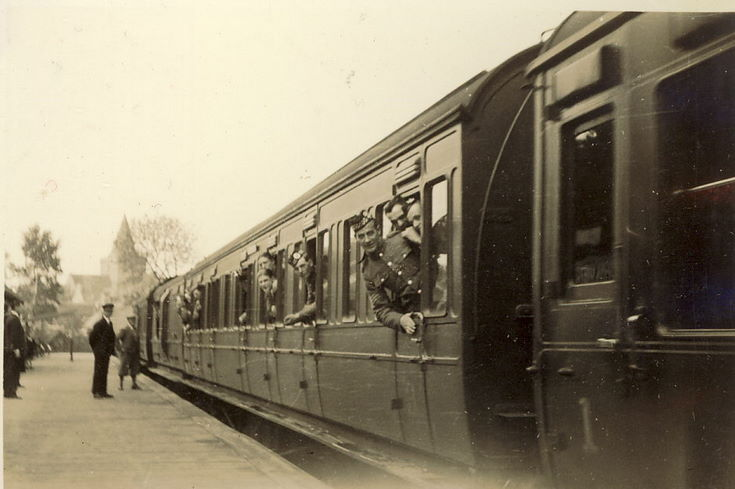 Train at Dornoch Station, with soldiers looking out of the windows