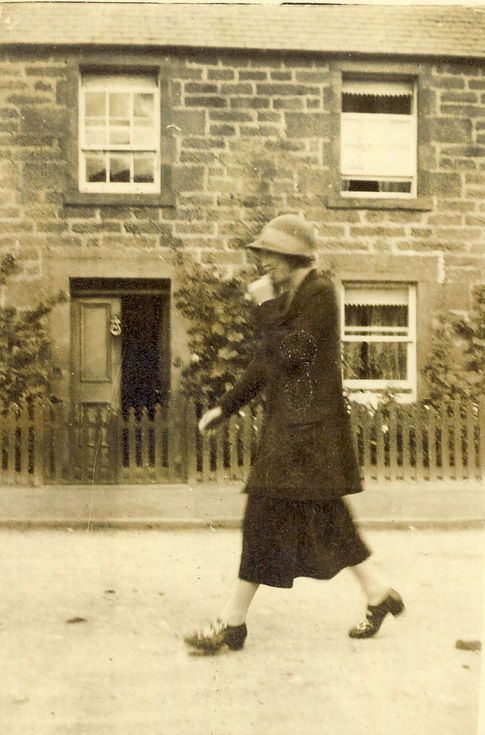 Lady walking in front of a house