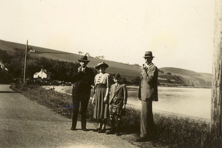 Two men, a woman, and a boy standing in front of a loch