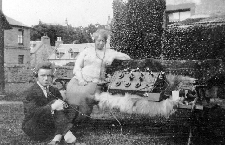 Man and woman, with headphones connected to an early radio set