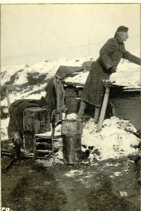 Colonel Robertson scrapes snow from the roof of H.Q.'s Hut