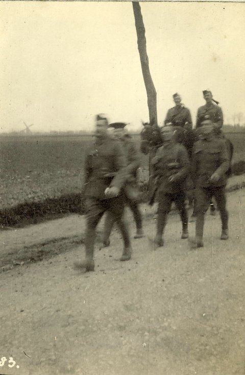 Soldiers marching with officers behind mounted