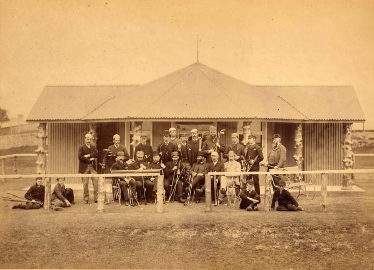 Photograph of a group of golfers in front of the original clubhouse in the late 1880s